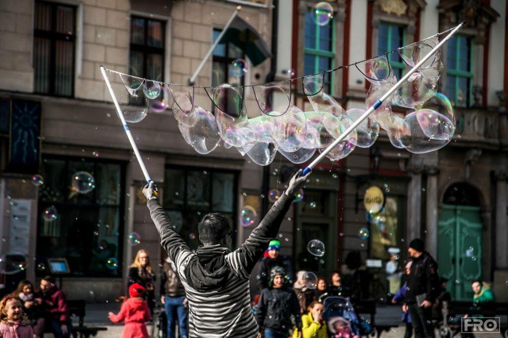 Uradowane dzieci obserwują puszczającego bańki mężczyznę znajdującego się na ulicy.
