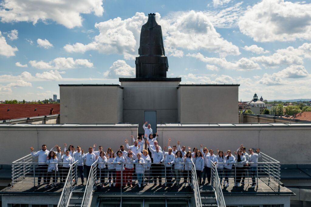Pracownicy WILiGZ stoją na dachu budynku ubrani w jednolite szare bluzy wydziałowe i machają ręką na powitanie. W tle widać niebo oraz panorame Krakowa.